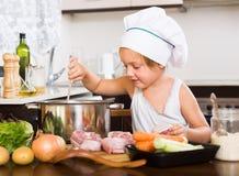 Babymeisje het koken met vlees Stock Afbeelding