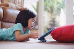 Babymeisje het letten op films op tablet stock foto's