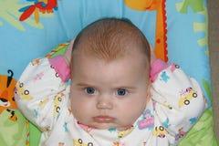 Babymeisje het ontspannen met handen achter haar hoofd Stock Foto's