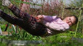 Babymeisje het spelen in de hangmat dichtbij huis langzaam-mo stock footage