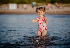 Babymeisje het spelen met een water Stock Fotografie