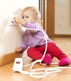 Babymeisje het spelen met elektrouitbreiding stock foto's