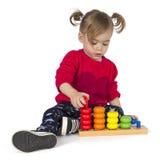 Babymeisje het spelen met ringenstuk speelgoed Stock Foto's