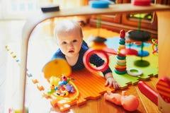 Babymeisje het spelen met speelgoed op de vloer stock afbeelding