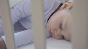 Babymeisje 2 jaar oude slaap in een voederbak behandelde witte deken Dagslaap stock videobeelden