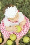Babymeisje met appelen in de tuin Stock Afbeelding