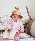Babymeisje met een boek van de hoedenlezing op bank royalty-vrije stock foto