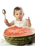 Babymeisje met lepel dichtbij de grote watermeloen Royalty-vrije Stock Foto's
