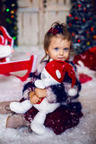 Babymeisje met Teddybeerstuk speelgoed in een rood GLB in het nieuwe jaar thuis Stock Fotografie