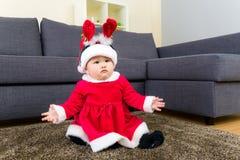 Babymeisje met x-mas vulling en zitting op tapijt Stock Foto's