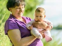 Babymeisje op de handen van haar grootmoeder Stock Foto's