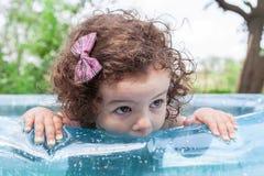 Babymeisje in opblaasbare pool Stock Afbeeldingen