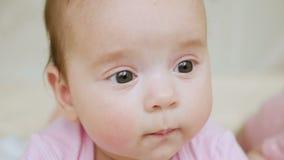 Babymeisje in roze kleren die op haar op zijn maag liggen stock footage