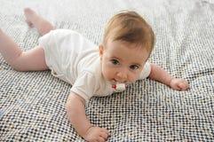 Babymeisje, vier maanden oud, op het bed met fopspeen stock fotografie