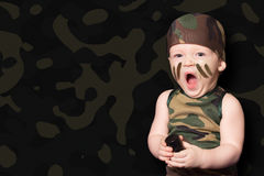 Babymilitair in eenvormig met oorlogsverf op zijn gezicht Jongen in unifo stock fotografie