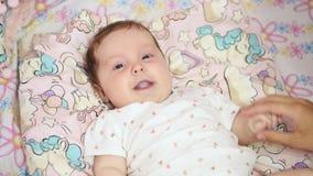 Babyniesgeluiden die op zijn rug op het bed liggen stock videobeelden
