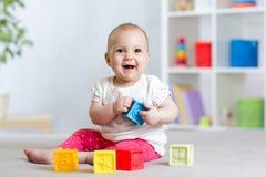 Babypeuter het spelen kleurenspeelgoed thuis of kinderdagverblijf Stock Afbeelding
