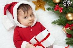 Babyporträt in der Weihnachtsdekoration, gekleidet als Sankt, Lüge auf Pelz nahe Tannenbaum und Spiel mit Geschenken, Winterurlau Lizenzfreie Stockbilder