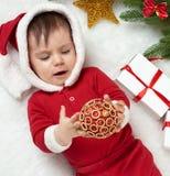 Babyporträt in der Weihnachtsdekoration, gekleidet als Sankt, Lüge auf Pelz nahe Tannenbaum und Spiel mit Geschenken, Winterurlau Lizenzfreie Stockfotografie
