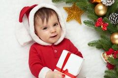 Babyporträt in der Weihnachtsdekoration, gekleidet als Sankt, Lüge auf Pelz nahe Tannenbaum und Spiel mit Geschenken, Winterurlau Stockfotos