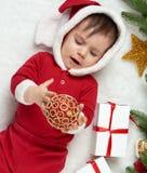Babyporträt in der Weihnachtsdekoration, gekleidet als Sankt, Lüge auf Pelz nahe Tannenbaum und Spiel mit Geschenken, Winterurlau Lizenzfreies Stockbild