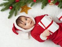 Babyporträt in der Weihnachtsdekoration, gekleidet als Sankt, Lüge auf Pelz nahe Tannenbaum und Spiel mit Geschenken, Winterurlau Stockfotografie