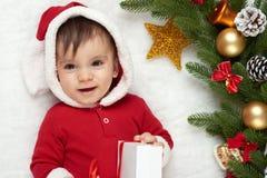Babyporträt in der Weihnachtsdekoration, gekleidet als Sankt, Lüge auf Pelz nahe Tannenbaum und Spiel mit Geschenken, Winterurlau Stockbilder