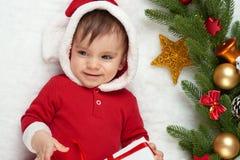 Babyporträt in der Weihnachtsdekoration, gekleidet als Sankt, Lüge auf Pelz nahe Tannenbaum und Spiel mit Geschenken, Winterurlau Lizenzfreies Stockfoto