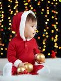 Babyportret in Kerstmisdecoratie, gekleed als Kerstman, boke lichten op donkere achtergrond, het concept van de de wintervakantie Royalty-vrije Stock Foto's