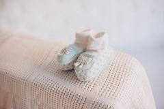 Babys bootees. Turquoise babys bootees in dots and with a bow placed on a white knitted rug on the armchair stock photos