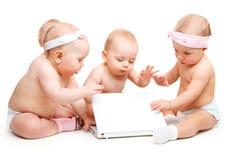 Babys die bij laptop werken stock foto's