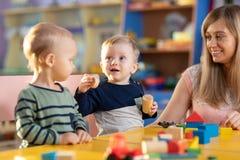 Babys, die mit Lehrer im Kindergarten oder in der Kindertagesstätte spielen stockfotos