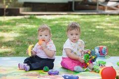 Babys, menos do que uns anos de idade, jogando com brinquedos Imagens de Stock Royalty Free