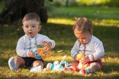 Babys, menos do que uns anos de idade, jogando com brinquedos Fotos de Stock Royalty Free