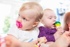 Babys mit Friedensstifter in der Krabbelstube, die mit Spielwaren spielt Lizenzfreie Stockfotos