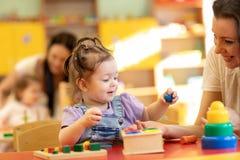 Babys mit Lehrern spielen mit Entwicklungsspielwaren in der Kindertagesstätte stockfoto