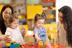 Babys spielen und ihre M?tter stehen im Spielzimmer im Kindertagesst?tte in Verbindung stockbilder