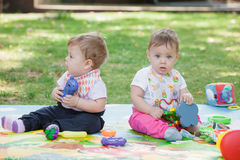 Babys, less than a year old, playing with  toys Royalty Free Stock Photo