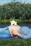 Babyschuhe auf schwangerem Bauch Stockfoto