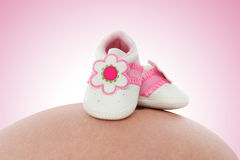 Babyschuhe auf schwangerer Frau Stockbild