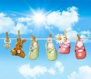 Babyschuhe, Friedensstifter und Teddybär betreffen Wäscheleine Lizenzfreies Stockfoto