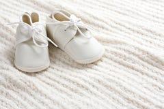 Babyschuhe und Decke Stockfotografie
