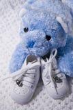 Babyschuhe und Teddybär Stockfotografie