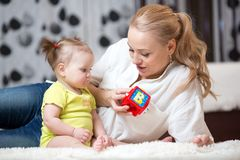 Babysitter and baby playing with toy cubes at home royalty free stock photos