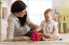 Babysitter and baby playing with toys in nursery. Babysitter and one year old baby playing with toys in nursery Stock Photo