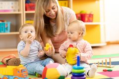 Babysitter and children play together in nursery or at home royalty free stock image