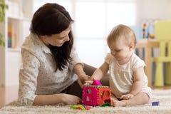 Babysitter die voor baby zorgen Kindspelen met sorteerdersstuk speelgoed zitting op het tapijt thuis royalty-vrije stock fotografie