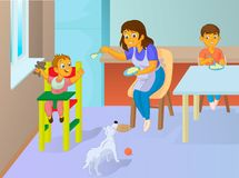 Babysitter feeding baby in the kitchen. With her dog Stock Images