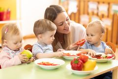 Babysitter feeding nursery babies. Toddlers eat healthy food in daycare. Center stock photo