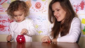 Babysitter and little cute child girl putting coins into piggy bank. Economical financial education concept. Static shot. 4K UHD stock video footage